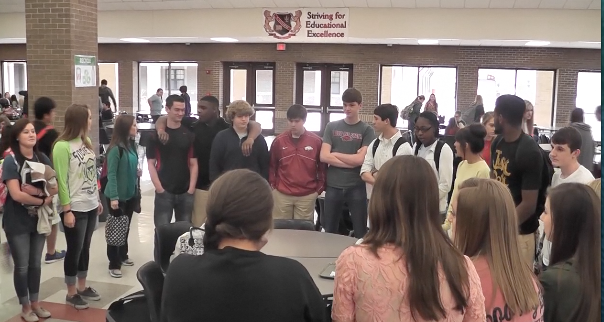 Students participate in prayer circle during lunch